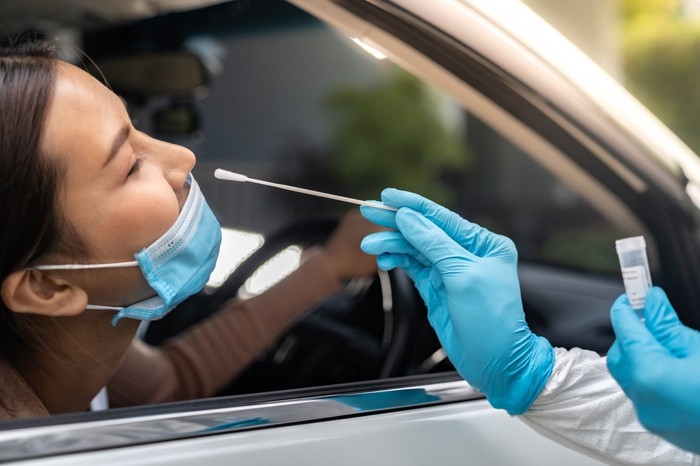 A woman leans out of the passenger side of a car for a COVID test.