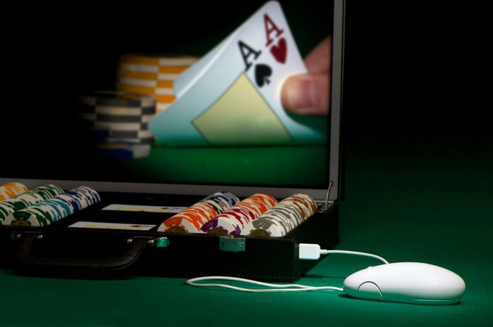 An online poker game showing a player's hand on a screen turning over a pair of aces.