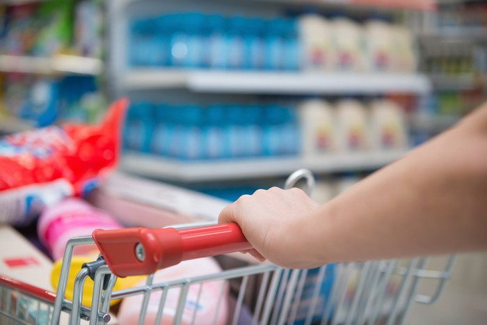 Hand gripping the handle of a nearly full grocery cart with shelves of blurry products in the background