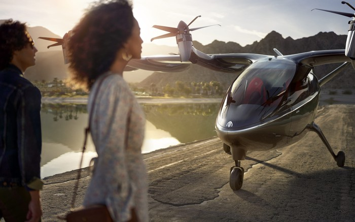 Two people next to an Archer electric plane.