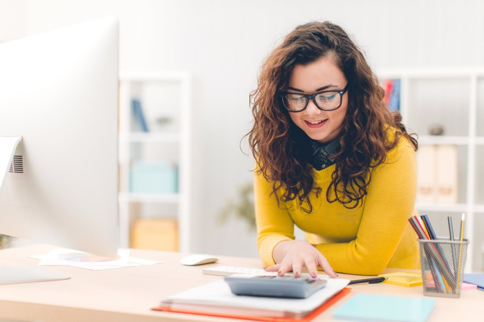 Woman wearing glasses and a bright yellow sweater leans over a desk, where she is using a calculator and standing in front of a large desktop monitor.