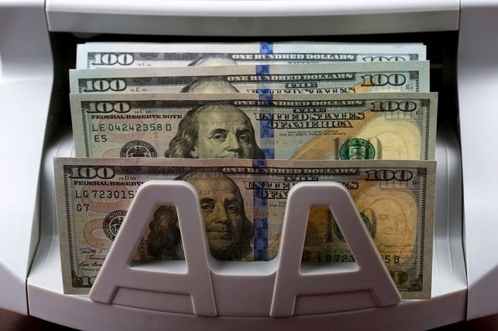 Hundred dollar bills are being dispensed by an ATM.