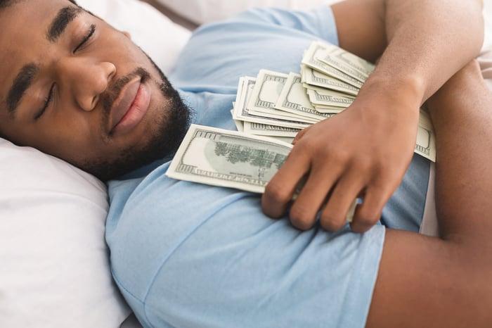 A man is sleeping, clutching hundred-dollar bills.