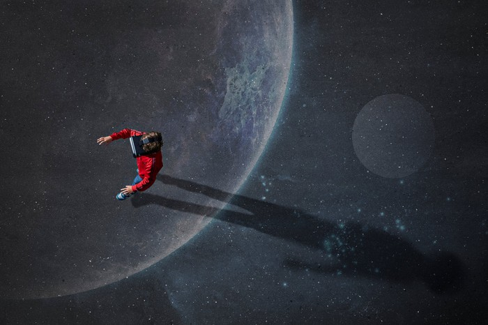 Person using a AR, VR, or MR headset advancing on a floor featuring a space motif.