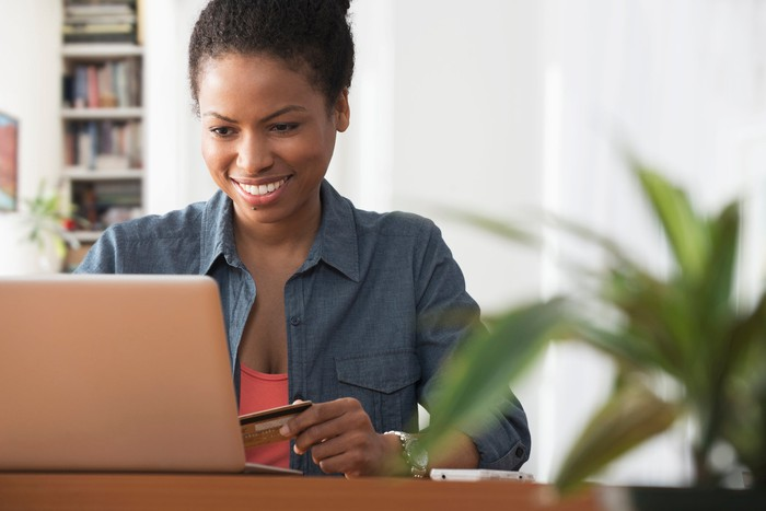 A woman holding a credit card in her left hand while looking at an open laptop.