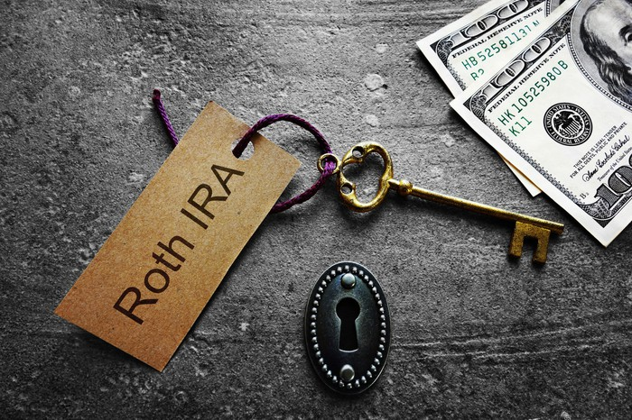 Gold key with Roth IRA tag, with keyhole and cash.