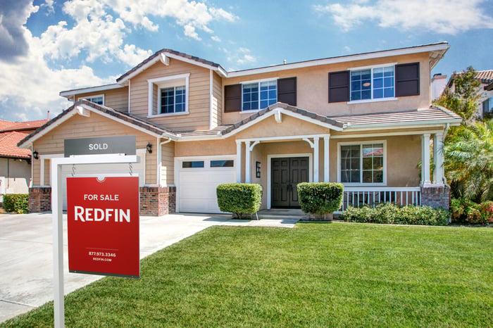 Un signe de liste de vente Redfin devant une maison de deux étages.