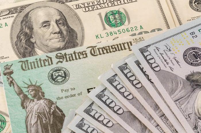 Une pile de billets de cent dollars en éventail couvrant partiellement un chèque du Trésor américain.