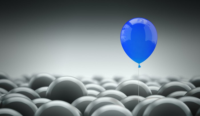Blue balloon sitting above room full of gray balloons