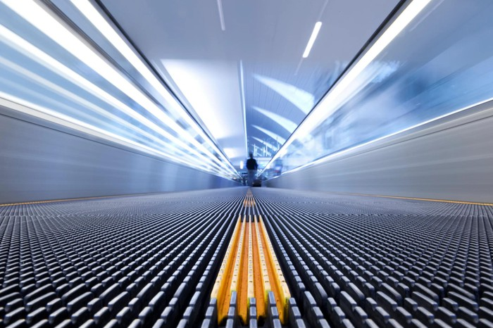 Moving walkway with focus on yellow center line.