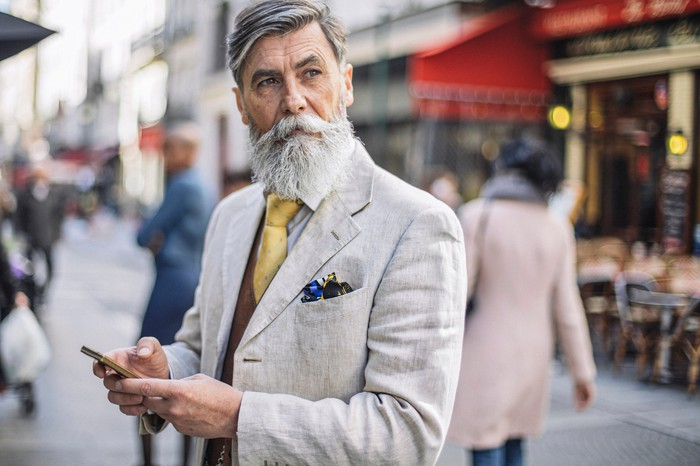 A bearded man texting in the street.