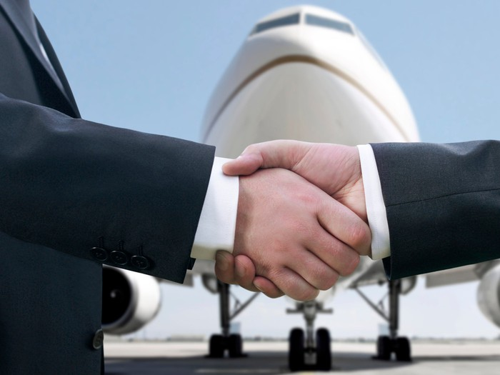 aircraft leasing agreement with handshake and plane in background