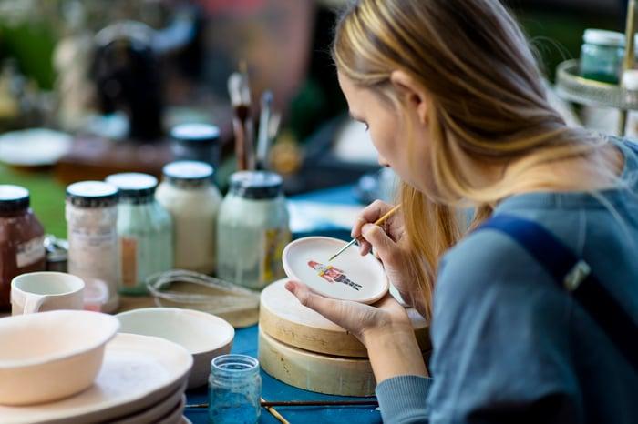 Dame mettant la touche finale à une peinture sur un dessous de verre à l'aide d'un pinceau fin.