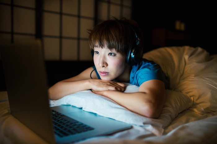 Young woman wearing headphones watching a program on her laptop as she lays in bed.