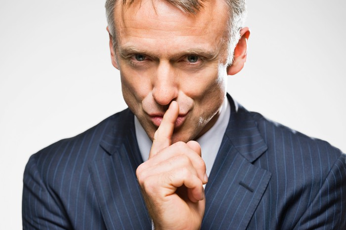 A man in a suit has his finger in front of his mouth, shushing others