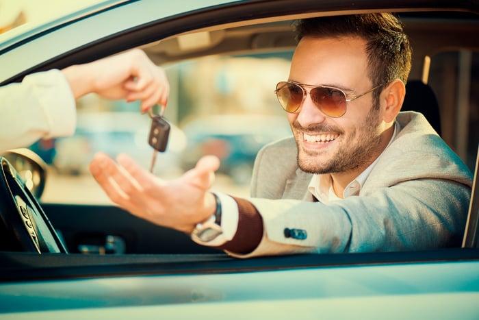 Someone handing keys to man sitting in car