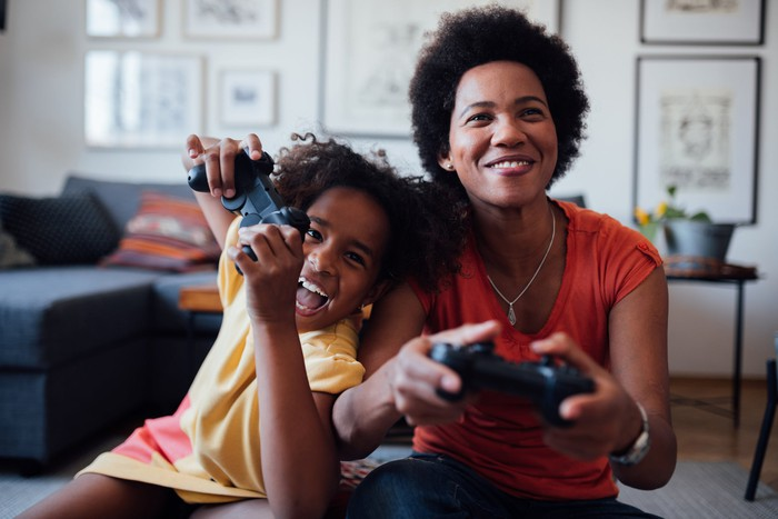 A mom and kid smiling and playing video games.