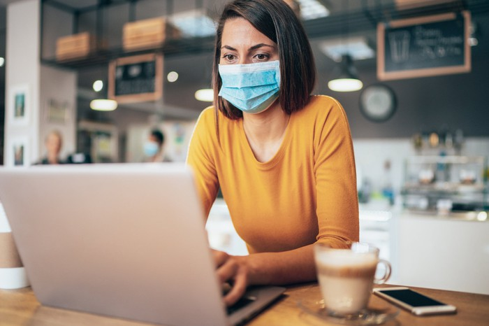 A woman in a medical mask works on her laptop in a coffee shop.