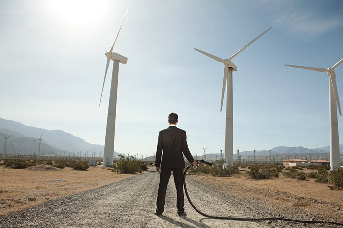 A man standing in the middle of a road holding a gas pump while gazing at a field of wind turbines.
