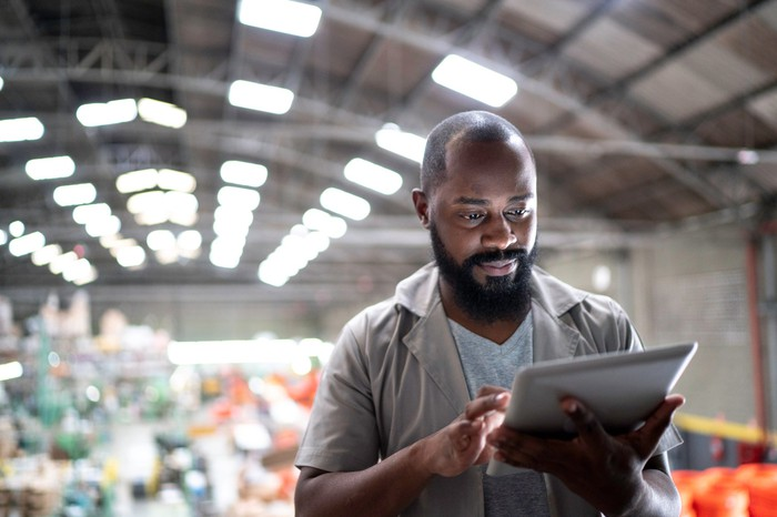 A man using a tablet in an industrial setting.