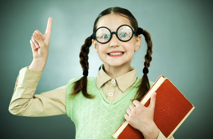 A young girl in glasses is holding up one finger and carrying a book.