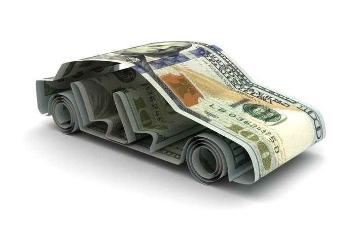 Multiple one hundred dollar bills folded and shaped to make a miniature car.