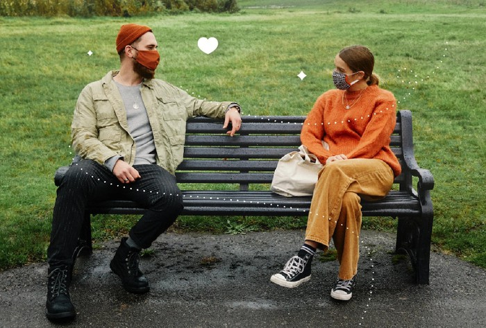 A couple in masks meeting in a park.