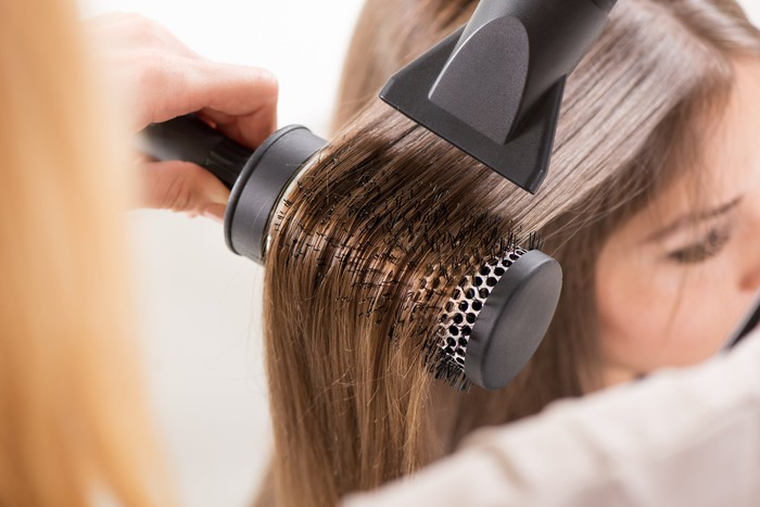 A salon customer having her hair blow-dried.