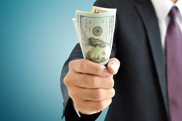 A man in a suit holds out a handful of money.