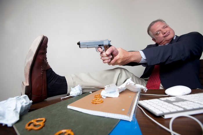 Man in suit sitting at desk aims pistol to shoot himself in the foot