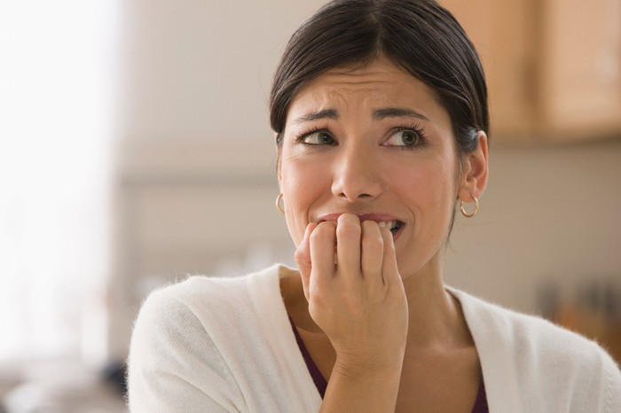 Closeup of woman with nervous expression biting nails