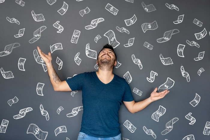 Excited man looking up as money is floating in the air.