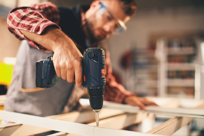 A man uses a drill during a home improvement project.
