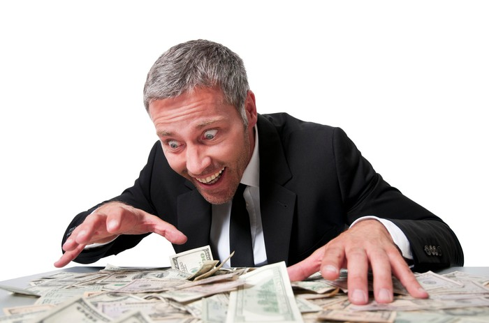 A smiling businessman hoards money.