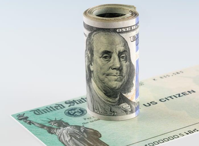 Roll of $100 bills on top of a U.S. Treasury stimulus check