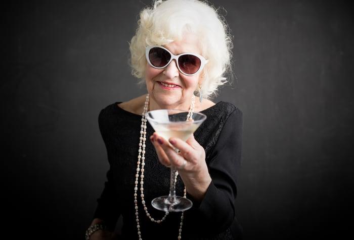 A senior woman in sunglasses enjoys a martini.
