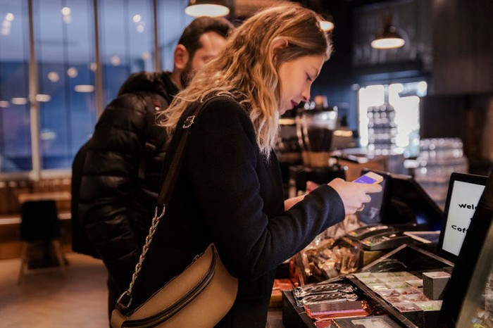Woman uses her mobile phone to order at a coffee shop.
