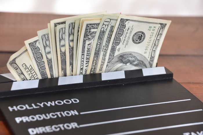 Movie clapperboard on top of cash