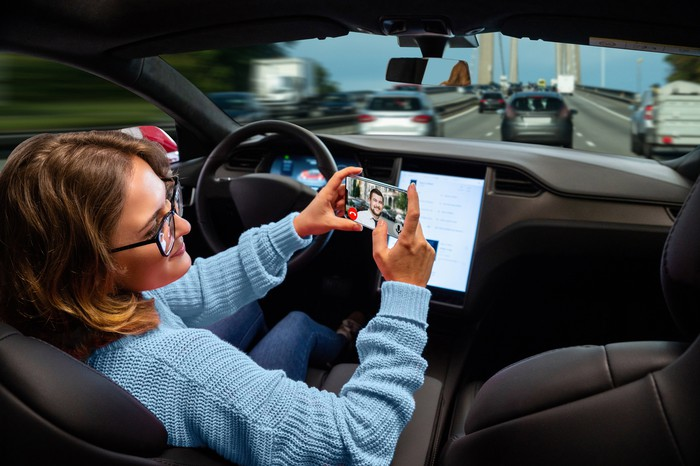 A woman using a phone while sitting in a self-driving car.