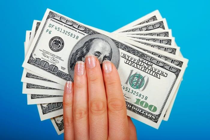 Une main bien entretenue tenant des billets de cent dollars.