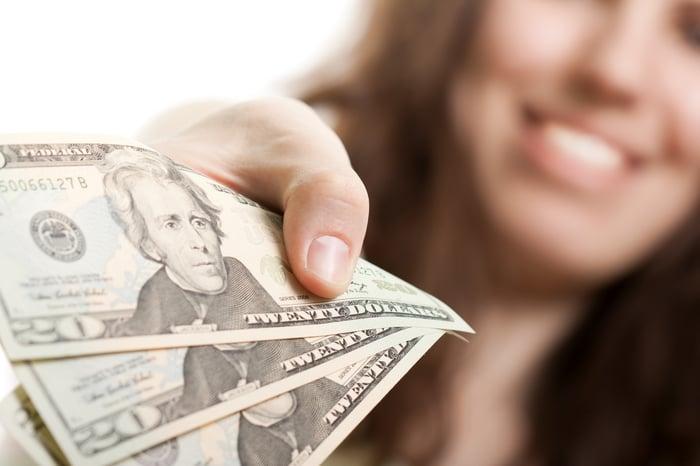 A woman handing over three $20 bills.