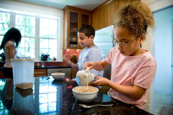 A young boy and girl eating cereal in a kitchen with a woman in the background