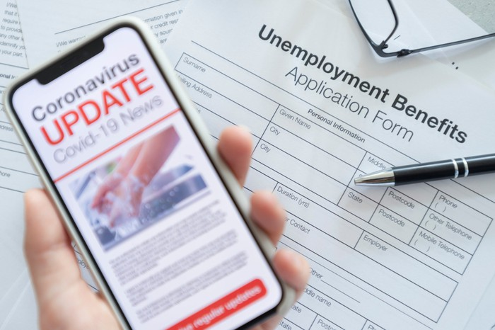 Unemployment benefits application and phone displaying COVID-19 news