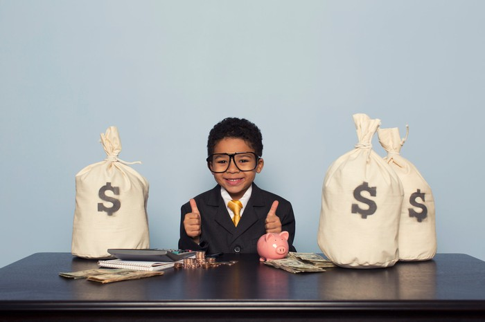 A happy young man in a suit and glasses sitting at a desk surrounded by bags of money.