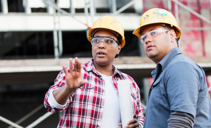 Two construction workers talking and looking into the distance.