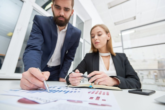 Man and woman working to prepare financial earnings restatements