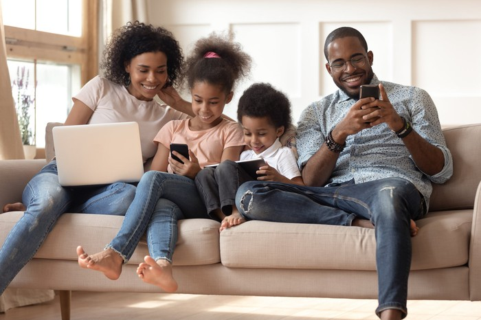 A family of four seated on a couch, each engaged with their own wireless device.