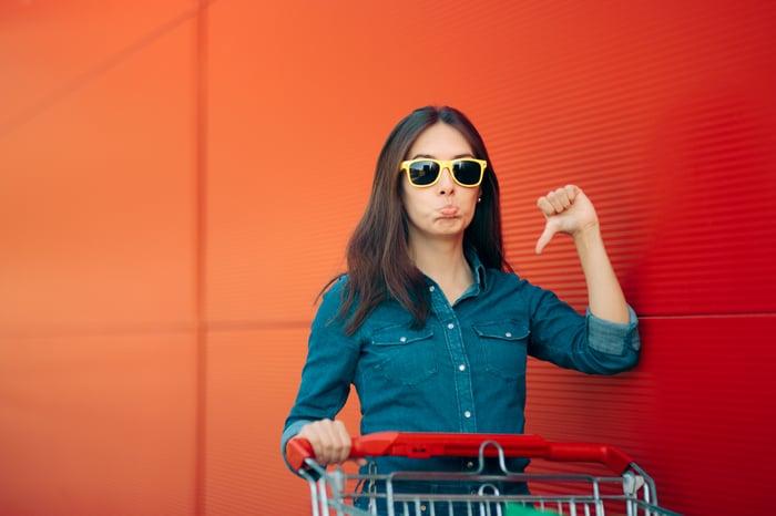 Une jeune femme à lunettes de soleil donne un signe de pouce vers le bas.