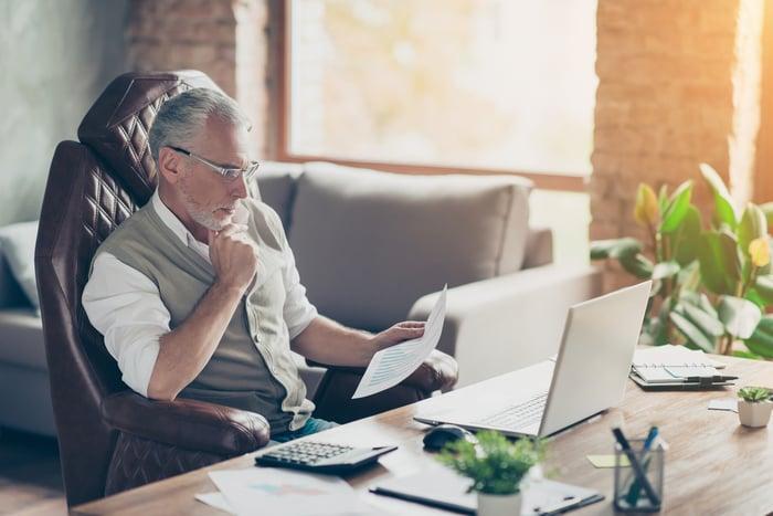 Un homme assis à un bureau et regardant un morceau de papier.