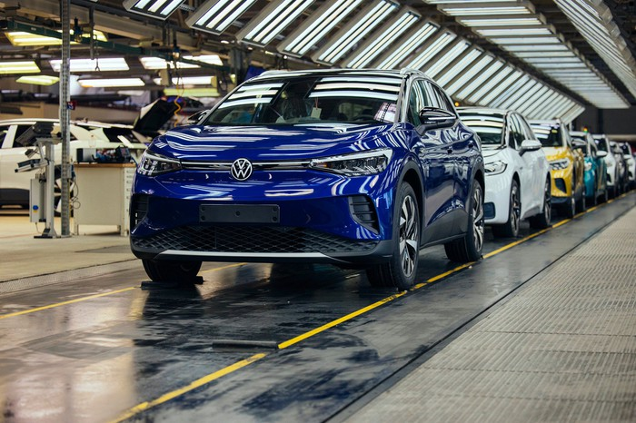 A blue Volkswagen ID.4, an electric SUV, leads a line of VW cars at the end of a factory assembly line.